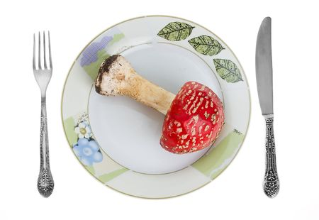 Red toadstool on dish with knife and fork. photo