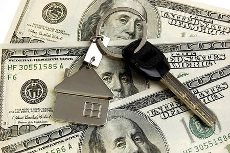 Real estate concept - keys on stack of dollars photo