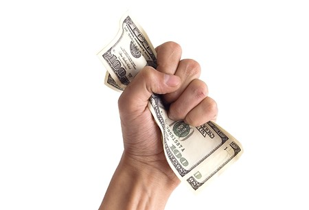 grabbing hand: financial concept - hand grabbing dollars isolated on white