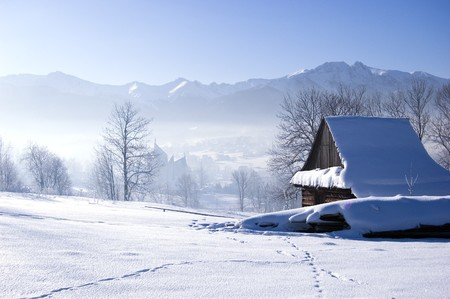 Winter scene in mountains. Old house and snow Stock Photo