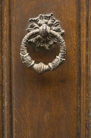 old knocker on weathered wooden door photo