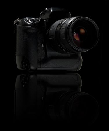 Professional digital camera over black background. With reflection. photo
