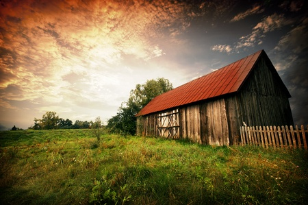 farmlands: Old wooden bar with red roof over the dramatic sunset. Zalew Zegrzynski, Poland Stock Photo