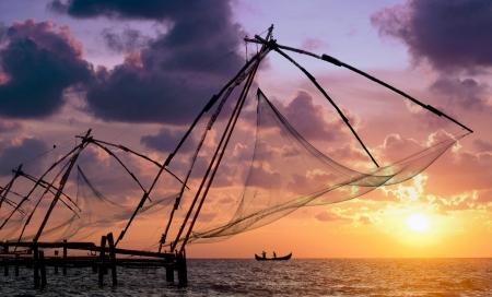 redes de pesca: Puesta de sol sobre las redes de pesca chinas y el barco en Cochin Kochi, Kerala, India