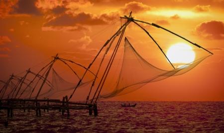 Puesta de sol sobre las redes de pesca chinas y el barco en Cochin (Kochi), Kerala, India.