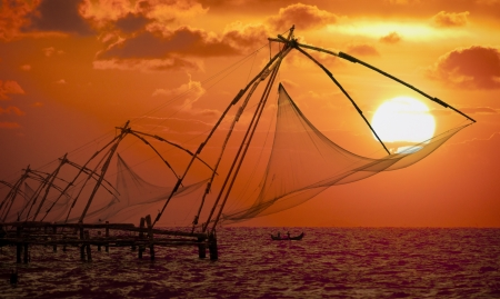 Sunset over Chinese Fishing nets and boat in Cochin (Kochi), Kerala, India. Stock Photo