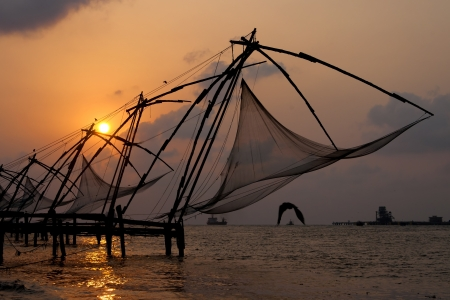 chinese fishing nets: Sunset over Chinese Fishing nets and boat in Cochin (Kochi), Kerala, India. Stock Photo