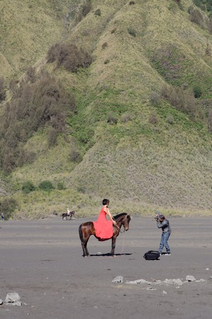 tengger: Undefined model posing on a horse under the Bromo massif. Mount Bromo is an active volcano and part of the Tengger massif in East Java. June 28 2014.