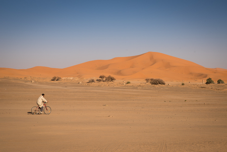 excursions: Hassilabied, Morocco - January 19th, 2016: Man riding on a bike in Hassilabied. Hassilabied is a popular tourist destination as a starting point of Sahara Desert excursions.