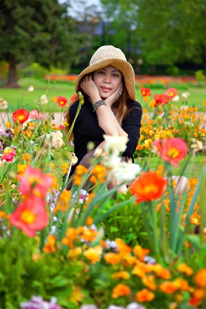 Contented Woman in a Field of Flowers Outdoors with a Hat