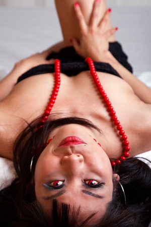 Portrait of Attractive Asian Woman Lying Down With Red Eyes and Necklace