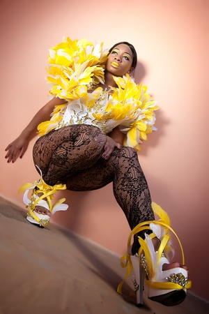 Sexy Female Squatting Against the Wall with High Heals Wearing Feather Outfit
