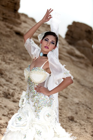 Beautiful Asian in a White Gown Posing Outside Holding a Veil