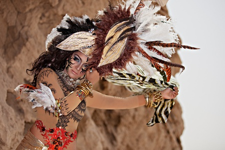 Tribal Female Wearing a Feather Head Gear and Holding a Stripe Veil Posing Outside Stock Photo