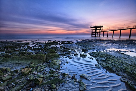 Beautiful, colorful sunrise along the coast during low tide