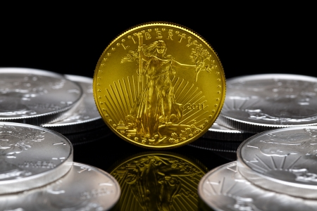 Uncirculated 2011 American Eagle Gold Coin with American Eagle Silver Coins. Stock Photo