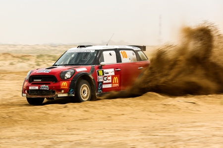 SAFIR, KUWAIT - April 13: A red Mini Cooper #10 participates in the Kuwait International Rally organized by The Quarter Mile Motorsports Club (QMMC) & Motorcycle Club on April 13, 2012 in southern Kuwait.