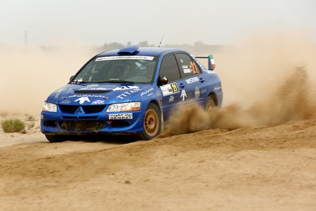 SAFIR, KUWAIT - April 13: A Mitsubishi #21 participates in the Kuwait International Rally organized by The Quarter Mile Motorsports Club (QMMC) & Motorcycle Club on April 13, 2012 in southern Kuwait. Editorial