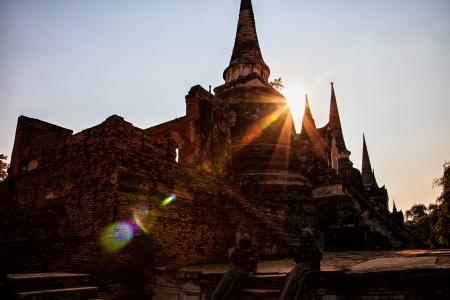 Ancient pagoda in Ayuttaya, Thailand with a sun starburst