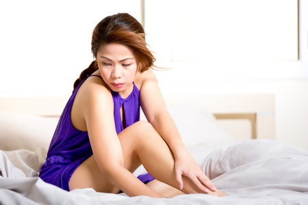 Asian woman wearing a purple outfit sitting in bed  Stock Photo