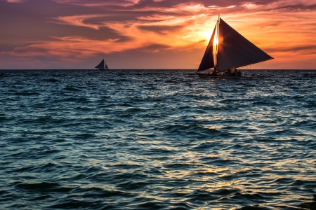 Sailboat sunset over the ocean water