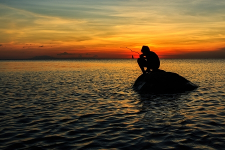 Silhouette of a boy squating on a rock fishing during sunset