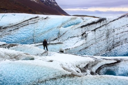 Lone man standing on a glacier