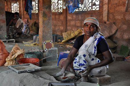 hombre pobre: Madurai, India - 7 de noviembre de 2009: una mujer no identificada trabaja duro en la f�brica de baldosas el 7 de noviembre de 2009. Este tipo de f�bricas es t�pica de la regi�n de Madurai en el sur de la India.