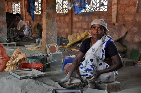 Madurai, India - 7 November 2009: An unidentified woman works hard in tile factory on November 7, 2009. This type of factories is typical for the region of Madurai on the south of India.