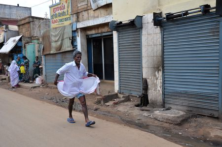Madurai, India - 7 November, 2009: An unidentified indian man in typical local men dress walks on the street in Madurai on November 7, 2009. Men on the south of India wear skirts. Stock Photo - 7659327