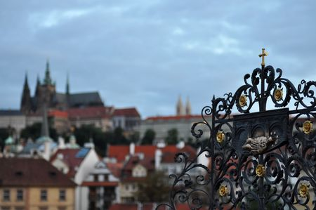 Iron ornament at Charles bridge with Prague castle on the background, Czech Republic. photo