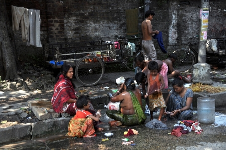 Kolkata, India - 27 October, 2009: An unidentified group of indian people wash themselves on the street of Kolkata on October 27, 2009.  Homeless living on the street are very common in every bigger city of India.