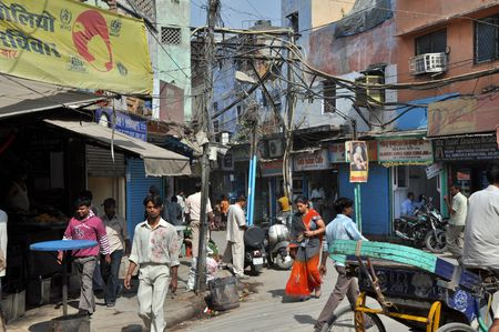 delhi: OLD DELHI, INDIA - 24 OCTOBER, 2009: An unidentified group of indian people travel under the risky and chaotic electrical wiring on October 24, 2009. Unsatisfying condition of wiring causes power problems in Delhi.