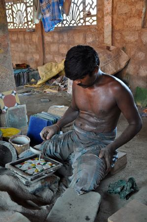 MADURAI, INDIA - 7 NOVEMBER 2009: An unidentified man works hard in tile factory on November 7, 2009. This type of factories is typical for the region of Madurai on the south of India.