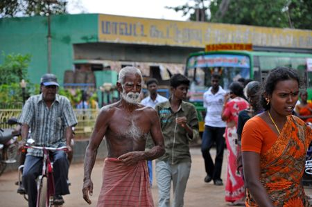 MADURAI, INDIA - 7 NOVEMBER, 2009: Poor indian man nearly without dress walks on the street in Madurai on November 7, 2009. Poverty is the serious problem in the whole India.