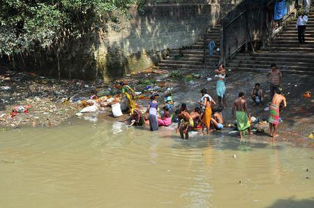 krottenwijk: KOLKATA, INDIA - 27 oktober 2009: een niet geïdentificeerde groep van Indische mensen wassen zichzelf in de rivier van de Hooghly op 27 oktober 2009. Op dit moment wordt deze rivier, net als de anderen in India enorm vervuild. Redactioneel