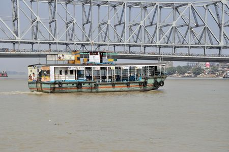 hooghly: KOLKATA, INDIA - 27 OCTOBER, 2009: An old ferry boat crosses the Hooghly River nearby the Howrah Bridge on October 27, 2009.  To use the ferry is easy, fast and cheap way how to cross the Hooghly River due to very often traffic jams on Howrah Bridge.
