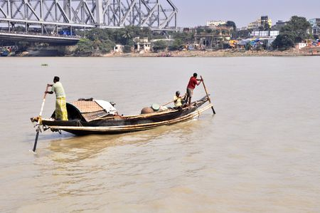 KOLKATA, INDIA - 27 OCTOBER, 2009: An old wooden ferry boat crosses the Hooghly River nearby the Howrah Bridge on October 27, 2009.  To use a small wooden ferry is easy, fast and cheap way how to cross the Hooghly River.