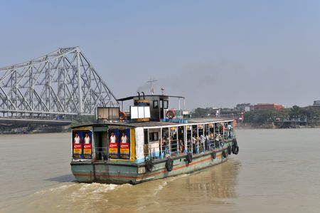 water transportation: KOLKATA, INDIA - 27 OCTOBER, 2009: An old ferry boat crosses the Hooghly River nearby the Howrah Bridge on October 27, 2009.  To use the ferry is easy, fast and cheap way how to cross the Hooghly River due to very often traffic jams on Howrah Bridge.