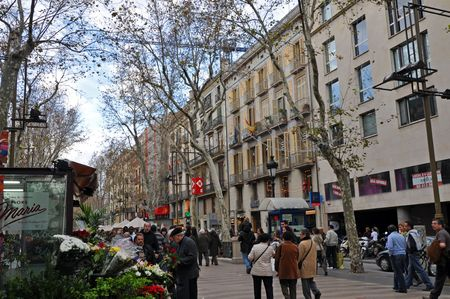 BARCELONA, SPAIN - 29 DECEMBER, 2009:  A group of tourists walk on La Rambla street on December 29, 2009.  The street is famous for shopping, eating and is also notorious for professional pick pockets.