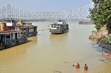 howrah: KOLKATA, INDIA - 27 OCTOBER 2009: An unidentified indian men wash themselves in Hooghly River on October 27, 2009. At present time this river, like the others in India, is being polluted tremendously.