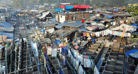 slum: DELHI, INDIA - 5 NOVEMBER, 2009: An unidentified Indian people work at Dhobi Ghat in Mumbai on November 5, 2009. Dhobi Ghat is the the worlds largest outdoor laundry and work there nearly 200 dhobi families.
