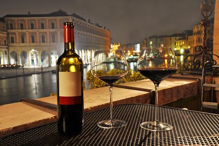 Glasses and bottle of a red wine in Venice.