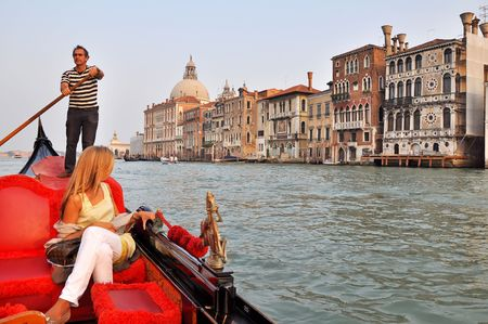 VENICE, ITALY - 29 SEPTEMBER 2009: An Italian gondolier navigates tourist through Venice in a gondola on the Grand Channel on September 29, 2009. The profession of gondolier is controlled by a guild, which issues a limited number of licenses.