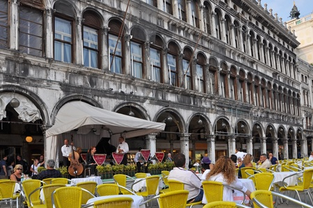 outdoor cafe: VENICE, ITALY - 30 SEPTEMBER, 2009: Tourists on San Marco square have a rest in one of many cafes with life music on September 30, 2009.  San Marco is the most famous and attractive square in Venice. Editorial