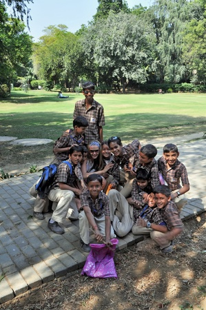 NEW DELHI, INDIA - 26 OCTOBER 2009: A group of Indian pupils pose with European tourist in the park in New Delhi on October 26, 2009. Education has been made free for children for 6 to 14 years of age in India.