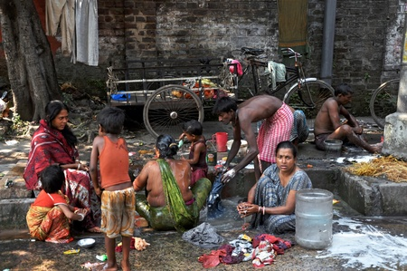 нищета: KOLKATA, INDIA - 27 OCTOBER, 2009: An unidentified group of Indian people wash themselves on a street of Kolkata on October 27, 2009.  Homeless living on the street are very common in every bigger city of India. Редакционное