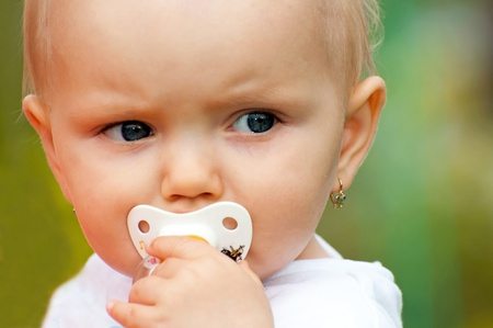 one eyed: Portrait of cute baby in the garden. Stock Photo