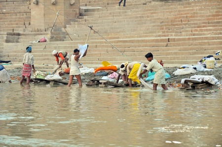 VARANASI, INDIA - 29 OCTOBER, 2009: An unidentified group of Indian people do the laundry in the river Ganga on October 29, 2009.  This type of outdoor laundry is typical for the whole India. Stock Photo - 8449035