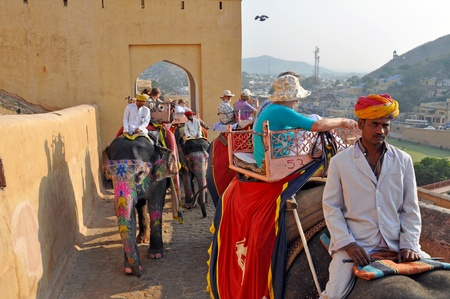 AMBER, INDIA - 4 NOVEMBER, 2009: Indian elephant riders ride with tourists to Amber Fort on November 4, 2009. On the ride, one can see the skyline of Jaipur, Maotha lake, and the original city walls.